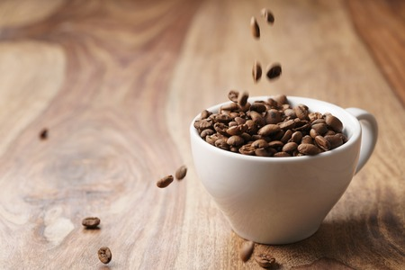 cappuccino cup with roasted coffee beans on wood table, with copy space