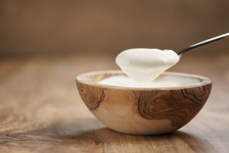 eating organic yogurt with spoon from wood bowl, 4k photo Stock Photo