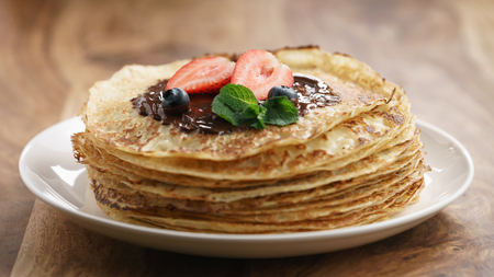 blini: fresh blinis or crepes with melted dark chocolate and berries, shallow focus