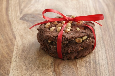 stack of homemade chocolate cookies with hazelnuts tied with ribbon on wood table, shallow focus