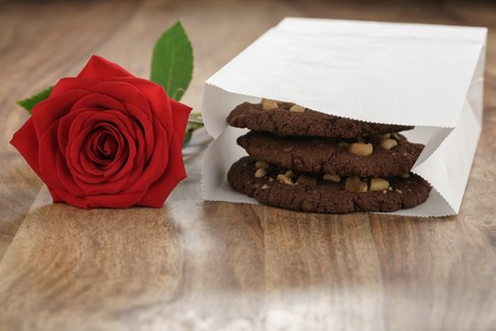morsels: homemade chocolate cookies with chocolate chips and hazelnuts with red rose on wood table, shallow focus