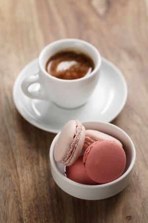 cup of fresh espresso with macarons on wood table, shallow focus