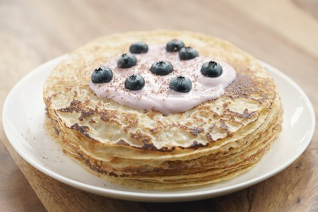 blini: blini with yogurt and blueberries on wood table, sweet breakfast