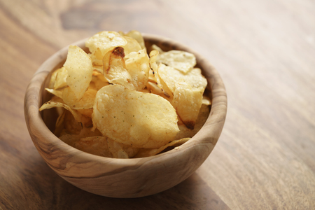 potato chips with herbs in wood bowl on rustic table Stock Photo