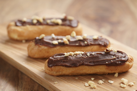 traditional french eclairs with chocolate and hazelnuts, shallow focus Archivio Fotografico