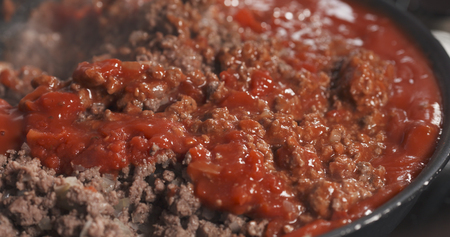 roasting pan: roasting minced beef with tomato paste in a pan, wide photo