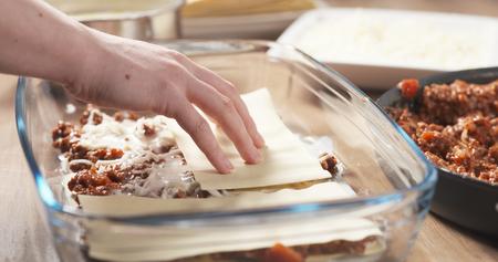 adding: preparing traditional italian lasagna adding pasta, wide photo