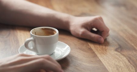 Young man hand with coffee cup waiting tapping fingers sitting at the table, wide photo