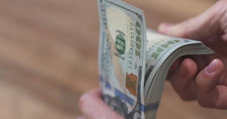 closeup man hands flipping dollars