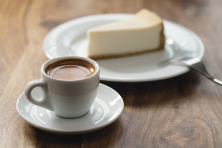 fresh espresso and cheesecake on table