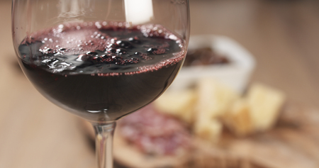 salame: red wine pour in front of italian antipasti appetizers