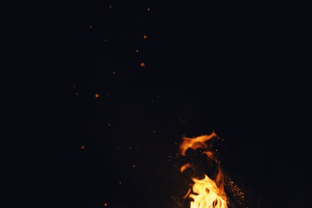 hot spark from campfire over night sky, shallow focus