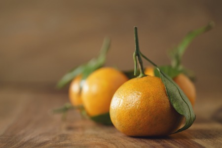 organic tangerines with leaves on wood table, shallow focus
