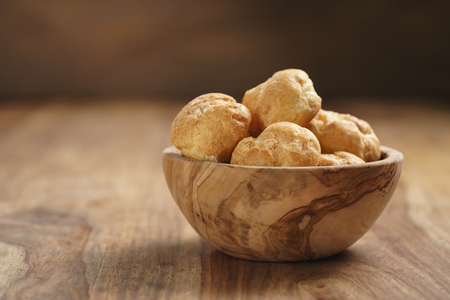 profiteroles in olive bowl on wooden table, shallow focus Stock Photo