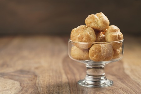 profiteroles in glass bowl on wooden table, shallow focus