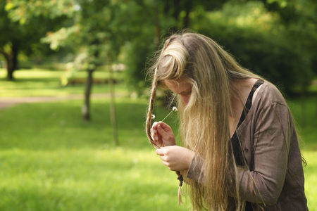 teen girl attach daisy flowers in hair in green park from behind in summer day, lifestyle portrait Stock Photo