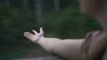 Handheld shot of teen girl hand enjoying and playing with wind from car, wide photo