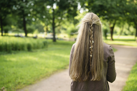 teen girl with daisy flowers in hair in green park from behind in summer day Stock Photo