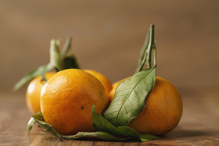 organic tangerines with leaves on wood table