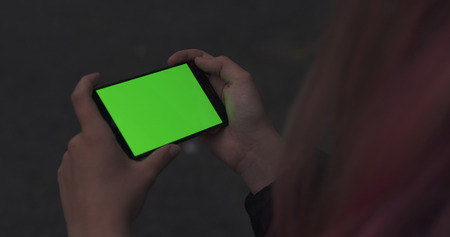 female teen girl holding smartphone with green screen outdoors Stock Photo