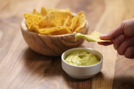 young female hand dipping nachos in guacamole sauce