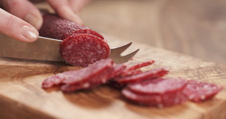 closeup female slicing thin salami sausage Stock Photo
