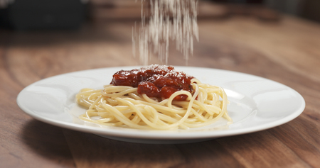 sprinkle grated aged parmesan cheese over spaghetti bolognese Stock Photo