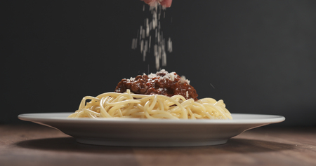 sprinkle grated aged parmesan cheese over spaghetti bolognese Stockfoto