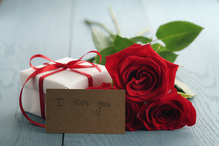 three red roses on blue wood table with gift and i love you paper card Foto de archivo