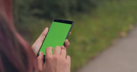 female teen holding smartphone with green screen on sidewalk in town