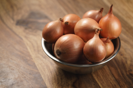 brown onions in steel bowl on old wood table Stock Photo