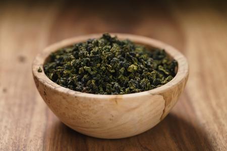 Dry organic green oolong tea in wood bowl