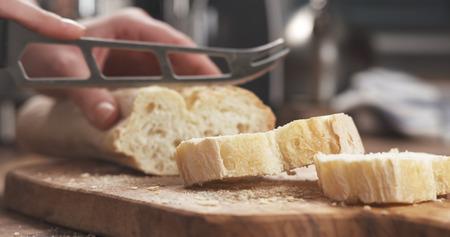 closeup slicing fresh baguette on cutting board Stock Photo