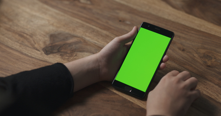 female teen girl holding smartphone with green screen sitting at the table