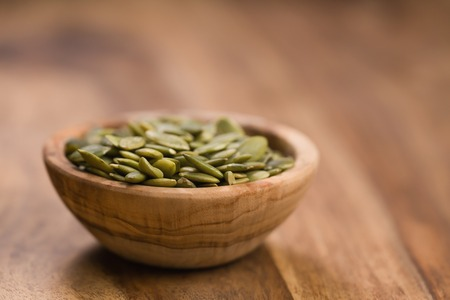 green pumkin seeds in bowl on wooden table Stock Photo