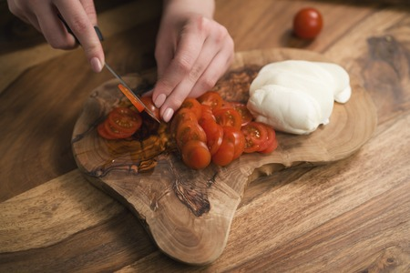 female teen hand slicing cherry tomatoes with knife on wooden board 写真素材