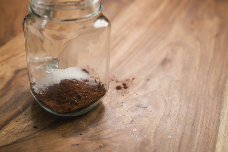 making cocoa drink in glass jar with handle on wood table, adding sugar Stock Photo