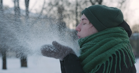 closeup of teen girl blowing snow from hands on cold winter day