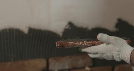 closeup worker applying concrete glue to brick cuts tile