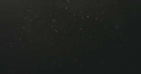 dust particles floating over black background with motion blur