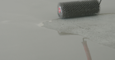 closeup using spike roller to remove air bubbles from self leveling floor Banco de Imagens