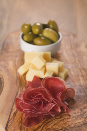 classic italian antipasti, breasola. olives and parmesan on olive board Standard-Bild