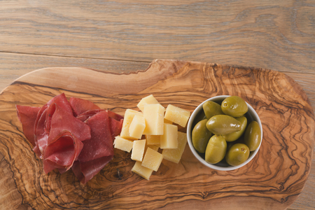 flat lay with classic italian antipasti, breasola. olives and parmesan on olive board