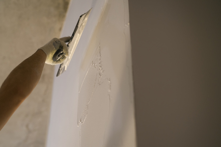 worker applying putty on the wall with putty knife