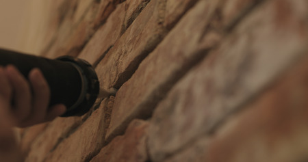 Slow motion closeup of worker filling seam between bricks with mortar from sealant gun