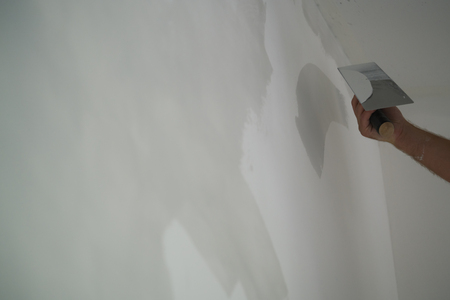 worker applying decorative concrete plaster on the wall