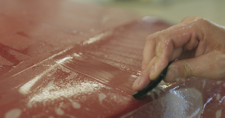 professional applying protective film to the red car