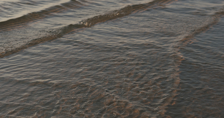 Closeup of small waves with caustics on a beach at sunset, wide photo Stock Photo
