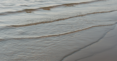 Closeup of small waves on a beach at sunset, wide photo