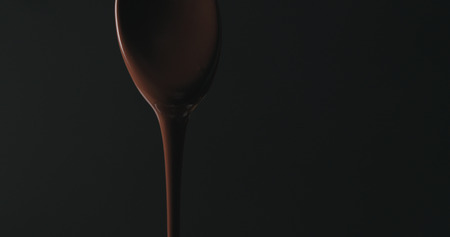 closeup melted dark chocolate dripping from spoon over black background Imagens